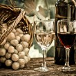 Wine bottles, two glasses and grapes in basket — Stock Photo