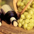 Red and white wine bottles and bunch of grapes — Stock Photo