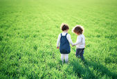 Children in spring field — ストック写真