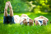 Happy children lying on green grass — Stock Photo