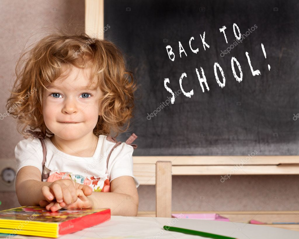 Happy smiling child in a class against blackboard with text Back to school! — Stock Photo #9152277