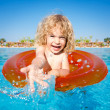 Happy child playing in blue water — Stock Photo