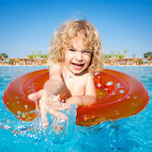 Happy child playing in blue water — Stok fotoğraf