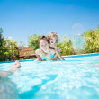 Happy family playing in swimming pool — Stock Photo