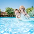 Happy child playing with mother in pool — Stock Photo