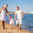 Happy family playing at the beach — Stock fotografie #9716339