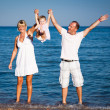 Happy family playing at the beach — Stock Photo