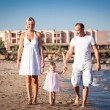 Happy family walking at the beach — Stock Photo