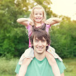Young man holding blonde little girl on shoulders in park in sum — Stock Photo