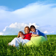 Happy kids and woman sitting outdoors — Stock Photo #10457998