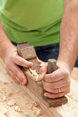 Carpenter or joiner working with plane — Stock Photo