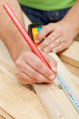 Carpenter or joiner measuring wood — Stock Photo