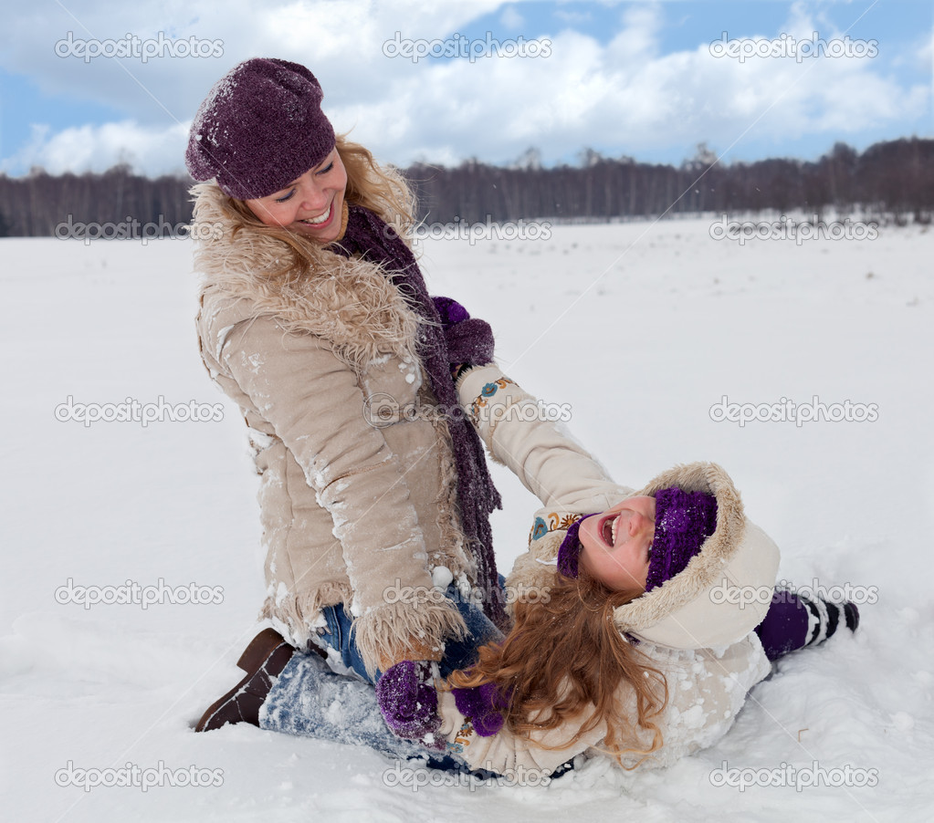 Woman and little girl having fun in the snow on a beautiful winter day — Stock Photo #8566917