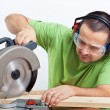 Carpenter cutting wooden plank — Stock Photo