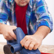 Stock Photo: Mworking wood with electric planer