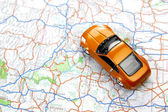 Orange sports car toy on map — Stock Photo