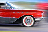 Fast moving classic red car — Stock Photo