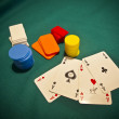 A selection of poker chips with 4 aces on a green felt background - Stock Photo