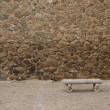 Foto Stock: Old stone wall with bench