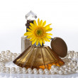 Stock Photo: VINTAGE PERFUME BOTTLES PEARLS & YELLOW FLOWER