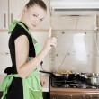 Young woman cooks dinner in the kitchen — Stock Photo #8125501