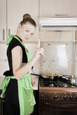 Young woman cooks dinner in the kitchen — Stock fotografie