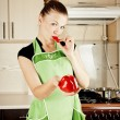 Foto Stock: Young woman cooks dinner in the kitchen