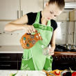 Stock Photo: Young woman cooks dinner in the kitchen