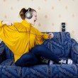 Stock Photo: Girl at home listening to music through headphones