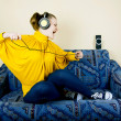 The girl at home listening to music through headphones — Stock Photo #9067118