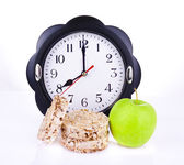 Dietetic loaves with green apple and watches at 8 o'clock — Stock Photo