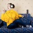 The girl at home listening to music through headphones — Stock Photo #9173974