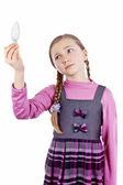 Little school girl looks at a light bulb — Stock Photo