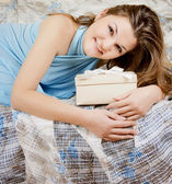 Portrait of happy girl sitting on bed giftbox in hands — Stock Photo