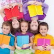 Happy kids laying on the floor holding books — Stockfoto #10382640