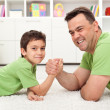 Постер, плакат: Father and son playing arm wrestling