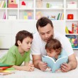 Father reading stories to his boys - Stock Photo
