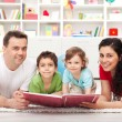 Young family with two kids reading a story book — Stock Photo