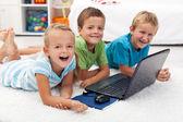 Glada barn med bärbar dator — Stockfoto