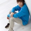 Teenager boy sitting on the floor by the wall — Stock Photo #8543390