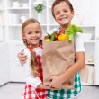 Happy healthy kids with the grocery bag in the kitchen — ストック写真