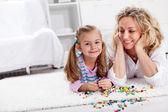 Hacer un collar para mamá - pequeña niña jugando — Foto de Stock