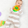 Baby girl playing on the floor chewing toys — Stock Photo