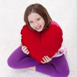 Young girl with large red heart pillow — Stock Photo #8808623