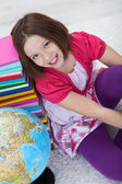 Happy school girl with books and globe — Stock Photo