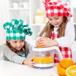 Little girls making fresh orange juice — Stock Photo #8815841