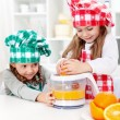 Little girls making fresh orange juice - Stock Photo