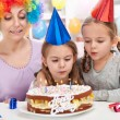 Birthday girl blowing out candles on a cake — Stock Photo #8815848