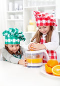 Little girls making fresh orange juice — Stock Photo