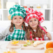 Little chefs slicing fruits in the kitchen — Stock fotografie